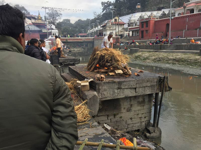 Attendant putting damp straw on the funeral pyre at the burning ghats at Pashupatinath