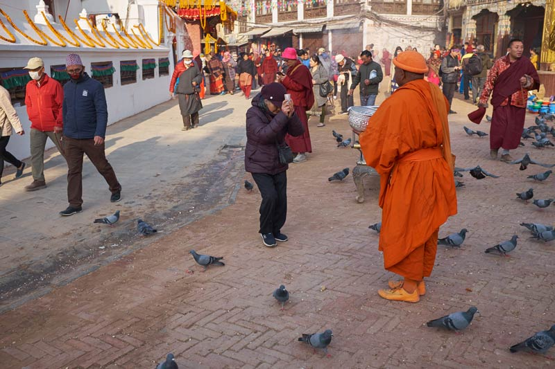 Person offering devotion and money to monk in Boudhanath.