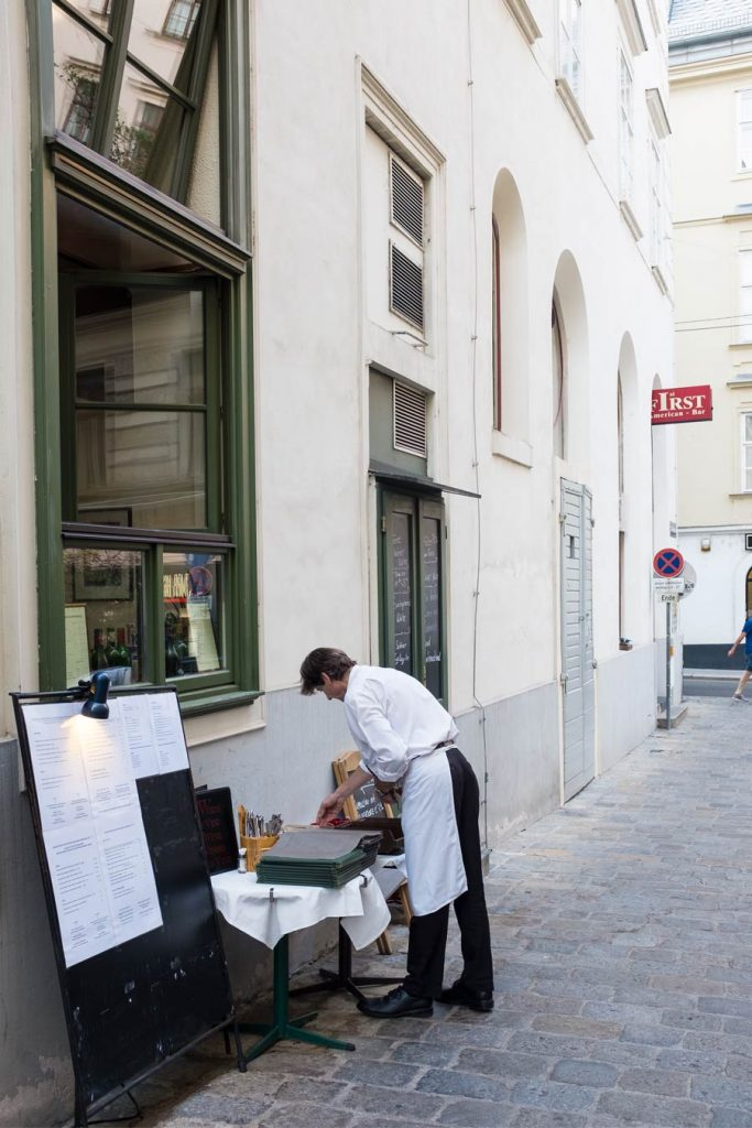 Man settling out the dining menu outside a restaurant in Vienna